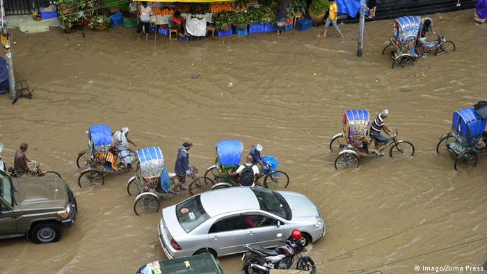 Vehicles and bikes try driving through the flooded streets of Dhaka after heavy rainfall caused by cyclone Roanu