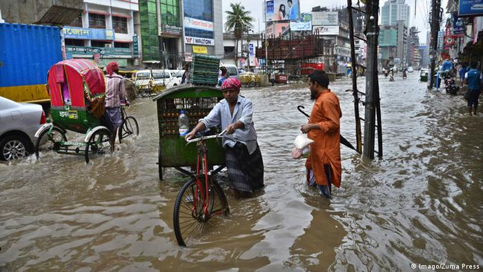 Vehicles try driving and citizens walking through the flooded streets of Dhaka after heavy rainfall caused a standstill in the streets to vehicles and commerce (Photo: Imago/Zuma Press)