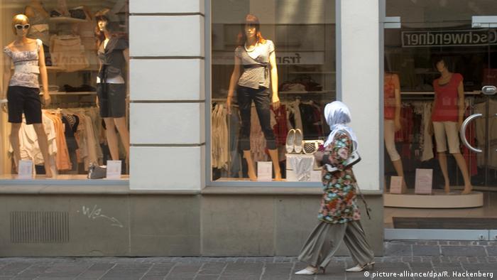 Deutschland Muslima mit Kopftuch vor Modegeschäft Symbolbild