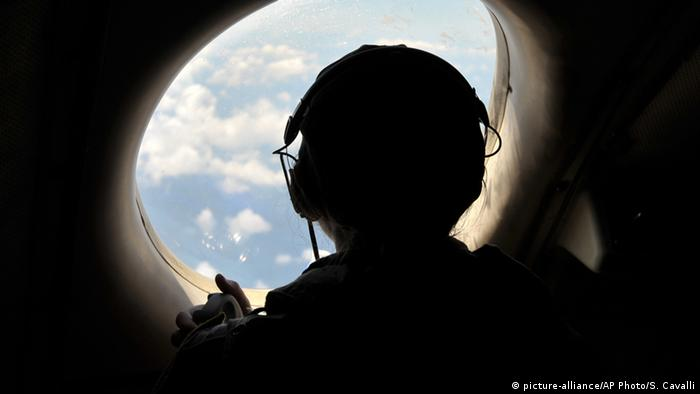 US Navy servicemember looks out of aircraft window during search operation for flight MS804 aircraft
