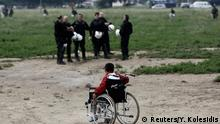 24.05.2016++++++Police operation to evacuate a makeshift camp for refugees and migrants near the village of Idomeni A refugee boy on a wheelchair passes in front of riot policemen during a police operation at a refugee camp at the border between Greece and Macedonia, near the village of Idomeni, Greece, 24 May 2016. (c) Reuters/Y. Kolesidis