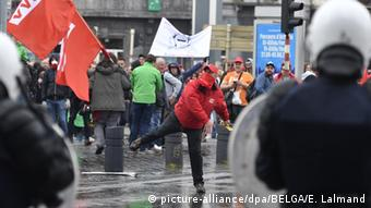 On a water soaked street, a Belgian protester in a red jacket and red hat has just hurled an object at police in Brussels.