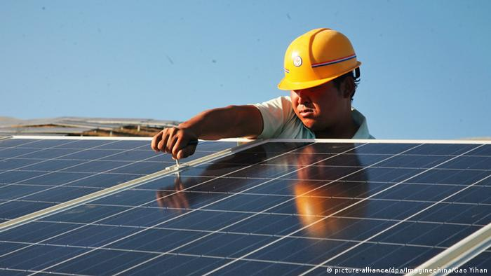 A worker with hard hat installing a solar panel