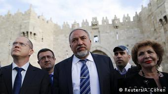 Avigdor Lieberman walking determinedly, surrounded by a group of men and women. (Photo: Reuters/A. Cohen)