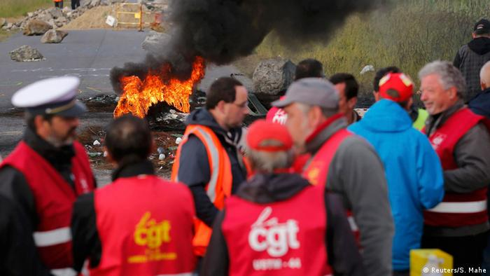 Striking French CGT labor union employees stand near a burning barricade to block the entrance of the fuel depot of the SFDM company near the oil refinery of Donges, France, May 25, 2016 in protest over proposed new labour laws
