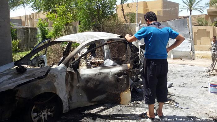 A man stands by a damaged car which was hit by a projectile launched by the Iraqi Force against the Islamic State militants in Fallujah, Iraq