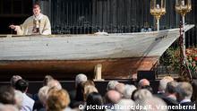 25.05.2016+++ Kardinal und Erzbischof Rainer Maria Woelki feiert am 26.05.2016 auf dem Roncalliplatz vor dem Dom in Köln (Nordrhein-Westfalen) an einem Flüchtlingsboot, das als Altar dient, eine Fronleichnamsmesse. +++ (C) picture-alliance/dpa/R. Vennenbernd