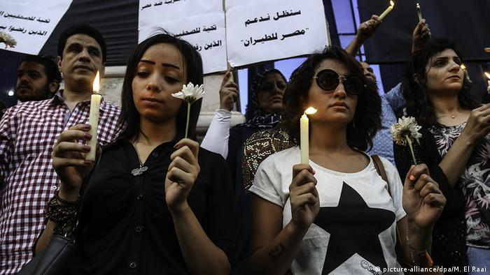People light candles during a commemoration ceremony for the 66 victims of EgyptAir flight MS804 crash