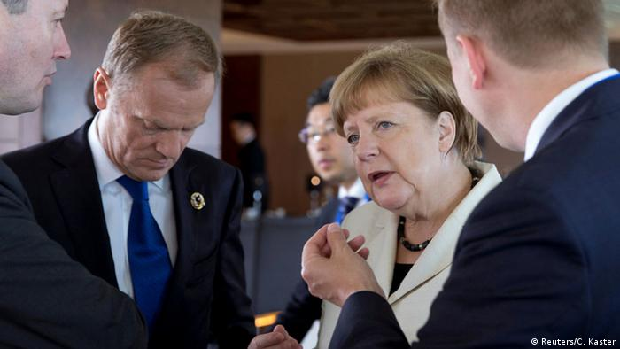 European Council President Donald Tusk, left, and German Chancellor Angela Merkel gather to participate in a G-7 Working Session in Shima, Japan