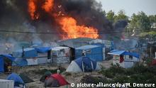 A shelter burns in the Calais 'Jungle' migrant camp in France