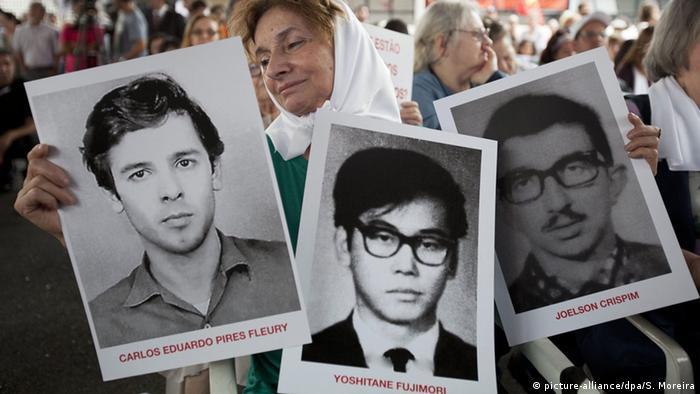 Em protesto em São Paulo, manifestante mostra fotos de pessoas desaparecidas durante a ditadura militar