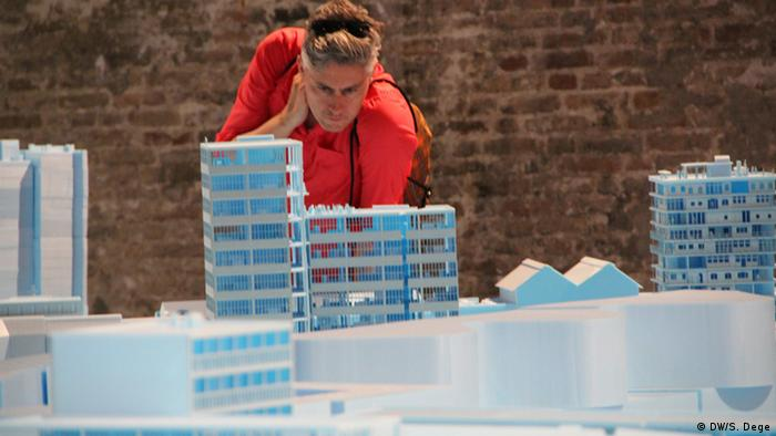 A visitor to Venice's Biennale of Architecture in 2016 wearing a orange shirt and staring at an architectural model.