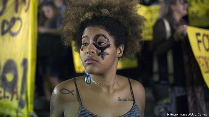 A woman wearing a female gender symbol attends a protest against the gang rape of a 16-year-old girl in Rio de Janeiro