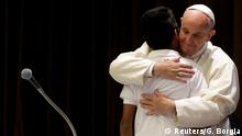 Papst Franziskus umarmt bei dem Treffen einen Jungen