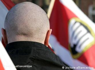 skinhead from behind with NPD flag in the background