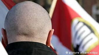 The back of a man with a skinhead holding an NPD flag