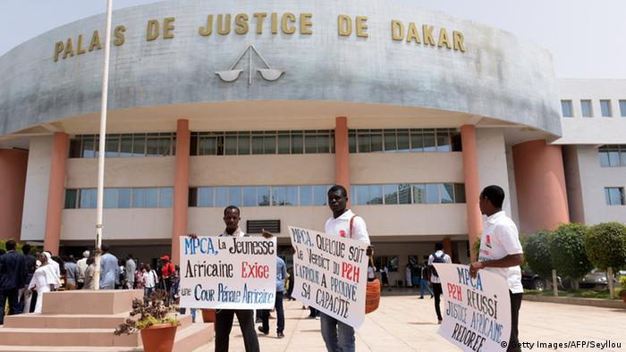 Activists of Peace Mobilization and African Justice hold placards reading Africa's youth asks for a African Criminal Court outside Dakar Courthouse