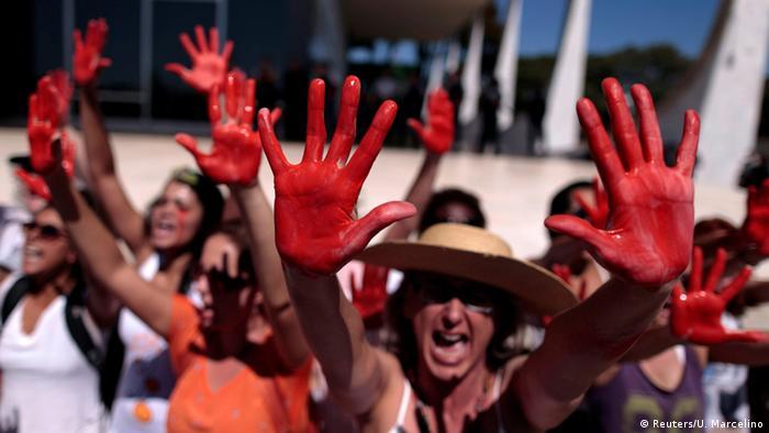 Manifestantes mostram mãos vermelhas de tinta em manifestação em Brasília em maio de 2016