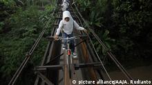 CENTRAL JAVA, INDONESIA - MARCH 11, 2014: Indonesian students go to school via suspension bridge that connects the Suro village and Plempungan village on March 10, 2014 in Boyolali, Central Java, Indonesia. The series of iron rods along the length of 30 meters and a width of 1.5 meters which is located 10 meters above the Pepe river is actually not a bridge, but the irrigation canals that drain water from the Cengklik reservoir to the surrounding rice fields. Built in the Dutch colonial period, people then use it as a bridge by adding sheets of wood over metal rods that ran above the water line. Students escape the danger while passing. Agoes Rudianto / Anadolu Agency | Keine Weitergabe an Wiederverkäufer. Copyright: picture alliance/AA/A. Rudianto