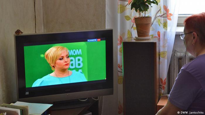 Женщина смотрит российский телеканал