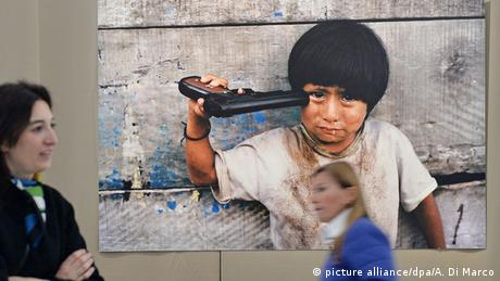 Boy with a toy gun to his head.