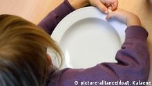 30.11.2012 *** ARCHIV - ILLUSTRATION - Ein Kind umklammert am 30.11.2012 seinen leeren Teller in einer Kita in Berlin und wartet auf das Mittagessen. Der Landtag in Düsseldorf befasst sich am 02. März mit dem Thema Kinderarmut in Nordrhein-Westfalen. Foto: Jens Kalaene/dpa (zu dpa/lnw: «Landtag debattiert über Kinderarmut, Sicherheit und Integration» vom 02.03.2016) +++(c) dpa - Bildfunk+++ Copyright: picture-alliance/dpa/J. Kalaene