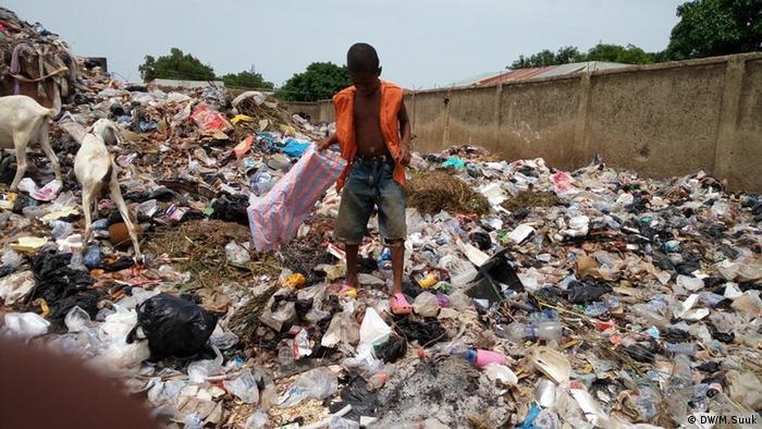 A young boy sifts through a garbage dumping site