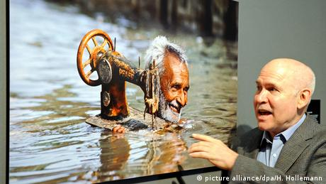 Steve McCurry holding the image of an Indian man during monsoon season