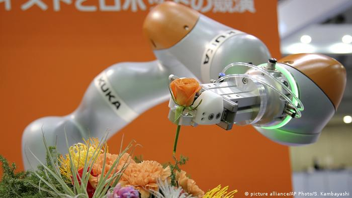 Japan KUKA Robotics LBR iiwa hält eine Blume bei einer Internationale Ausstellung in Tokio (picture alliance/AP Photo/S. Kambayashi)
