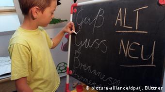 Ein junger Schüler steht vor einer Tafel und schreibt das wort guß nach alter und neuer Rechtschreibung. Außerdem das Wort Brennessel, bei dem er einen Buchstaben, das zweite s vergessen hat. picture-alliance/dpa/J. Büttner