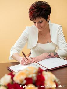 eine Frau im Hochzeitskleid sitzt auf einem Stuhl und unterschreibt im Standesamt die Heiratsurkunde. picture-alliance/dpa/H. Wiedl