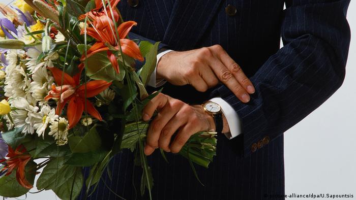 Mann im Anzug mit Blumenstrauß schaut auf seine Armbanduhr (Foto: picture-alliance/dpa/U.Sapountsis)
