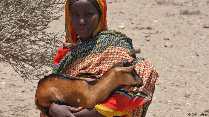 A colorful pastoralist carrying a goat
