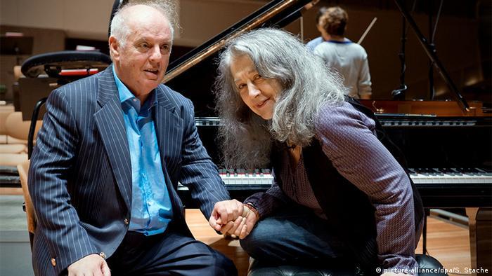 Daniel Barenboim y Martha Argerich tomados de la mano mientras están sentados al piano