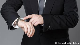 A man points at the watch on his wrist