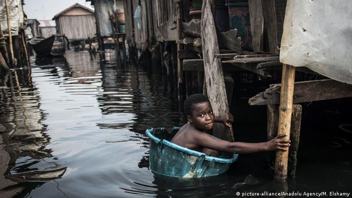A young boy in a plastic pail movbes through the dirty water of the Makoko slum
