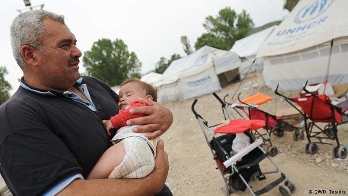 man holding baby copyright: Dimitris Tosidis