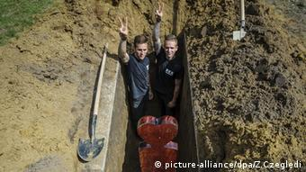 Gravediggers flash the victory sign while standing in a grave during the first National Grave Digging Competition in Hungary