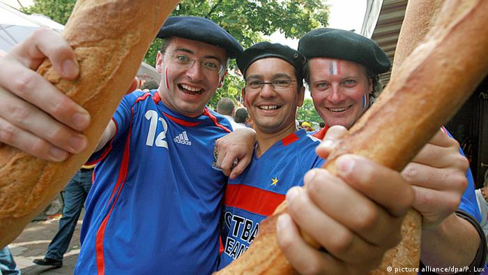 French football fans hold up baguettes before a football game with Spain
