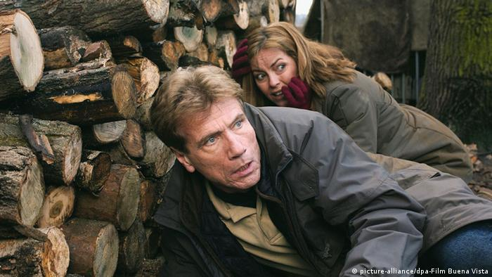 Jürgen Prochnow in the film Baltic Storm, along with actor Greta Scacchi, huddling before a pile of wood.