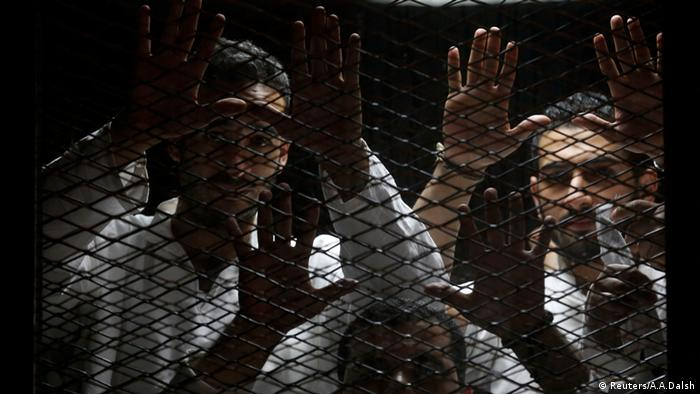 Jailed Egyptian journalists stand behind bars during their trial (Reuters/A.A.Dalsh)