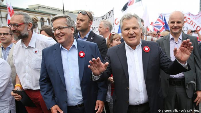 Former Presidents Bronislaw Komorowski (2-L) and Aleksander Kwasniewski (2-R) with KOD leader Mateusz Kijowski (L) participate in the march organised by Polish Committee for the Defence of Democracy (KOD) at the Bank Square in Warsaw