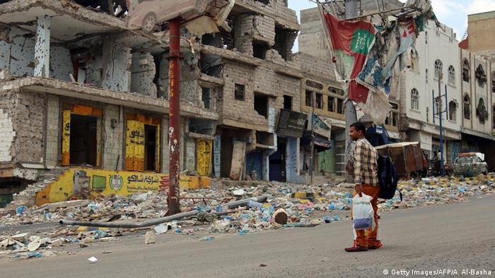 A man stares at a row of bombed out buildings on a street in Yemen's third city Taez.