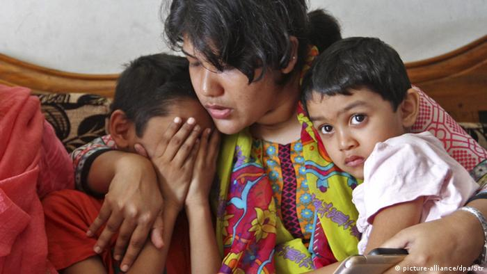 A relative consoles the children of Mahmuda Khanam Mitu after she was murdered in Chittagong, Bangladesh