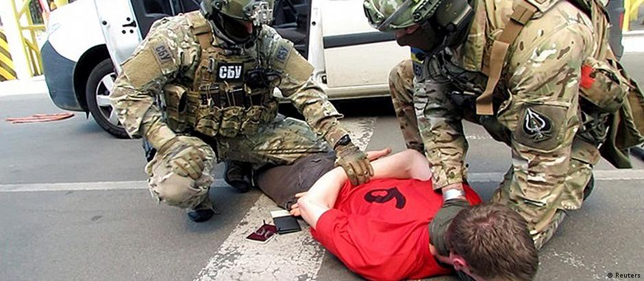 Policiais ucranianos no momento em que prenderam o francês, que tentava cruzar a fronteira com a Polônia rumo à França