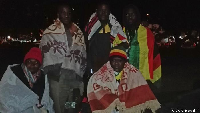 Activists of the 'Occupy Africa Unity Square' wrapped in national flags at night in Harare