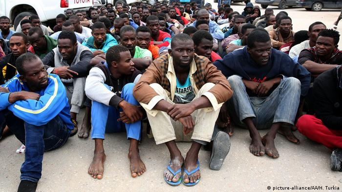 A group of African refugees sitting on the ground