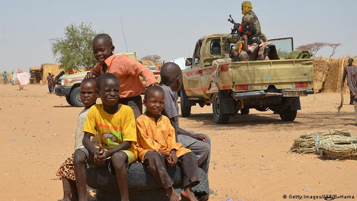 Children sit on an old tire in a refugee camp in Niger