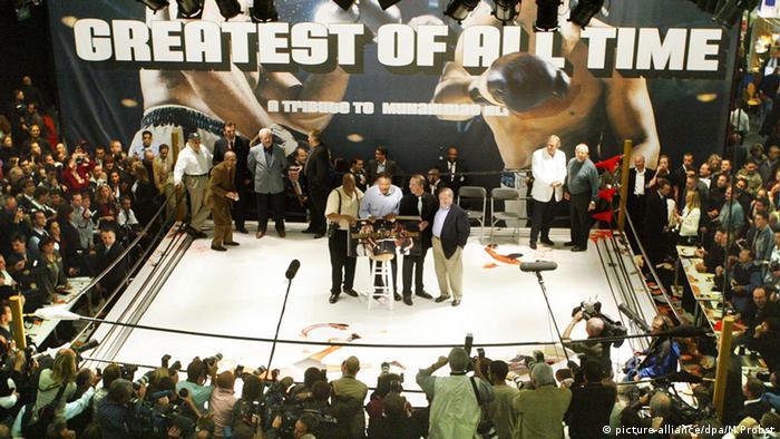 Muhammad Ali (li.) und Verleger Benedikt Taschen (2. v. re.) bei der Präsentation von Greatest of All Time auf der Buchmesse in Frankfurt in einer Art Boxstadion.