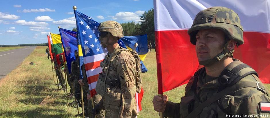 Soldados com bandeiras de todos os países da Otan enfileirados na fronteira leste da Aliança